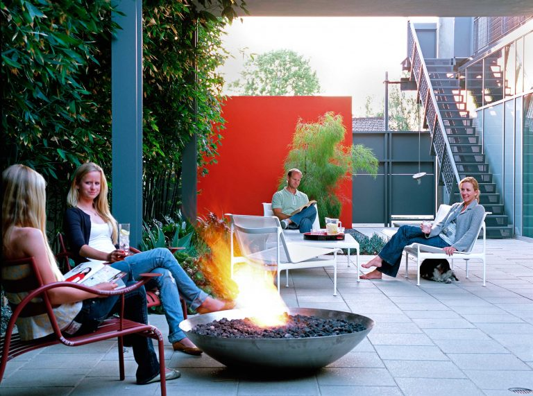Family gathered around a firepit in this exquisite CA backyard